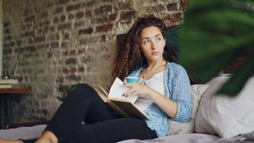 Pretty young lady is reading book in bed holding cup of tea and resting on pillows enjoying day at home. Beautiful loft. Pretty young lady is reading book in bed stock video footage