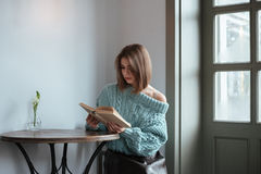 Pretty young lady sitting in cafe and reading book. Image of pretty young lady sitting at the table in cafe and reading book Stock Image
