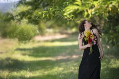 Pretty young lady stands under a tree holding a bouquet of wild flowers stock photos