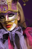 Pretty young lady in violet half mask. May be use for joker concept Stock Photography