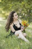 Pretty young lady sitting on grass holding a bouquet of wild flowers stock image