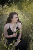 Pretty young lady among large weeds field stock image