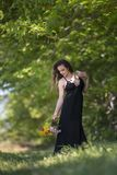 Pretty young lady stands under a tree holding a bouquet of wild flowers stock image
