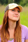 Pretty young lady wearing hat. A pretty young lady with long brown hair wearing a ball cap, standing in tall grass gazing off, day dreaming. Shallow depth of Royalty Free Stock Photo