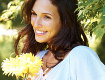 Pretty young lady with yellow flowers in a park Stock Photo
