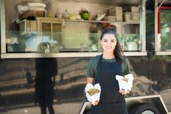 Oriental food truck owner. Pretty young Latin woman and oriental food truck owner showing some of her food with a smile royalty free stock photography