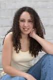 Pretty Young Latina with Curly Hair. And hand on cheek, sitting on steps Royalty Free Stock Images