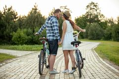Pretty young loving couple is walking in park stock images