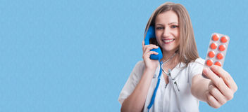Pretty young medic talking on telephone royalty free stock image