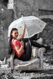 Pretty girl with umbrella sitting in chair. Pretty young model girl with umbrella and cigarette sitting in chair royalty free stock photography