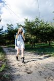 Pretty young model with long blond hair walking on the road in park royalty free stock image