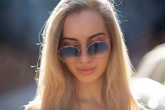 Pretty young model with long hair wearing glasses, posing at the street in sunny day stock image