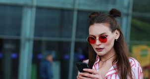 Pretty young model in red sunglasses takes a selfie on her smartphone stock video