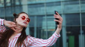 Pretty young model in red sunglasses takes a selfie on her smartphone. A beautiful girl stands next to the shopping stock footage