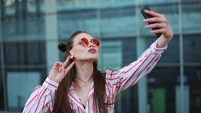 Pretty young model in red sunglasses takes a selfie on her smartphone. A beautiful girl stands next to the shopping stock video footage