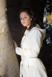 Pretty young model by tree. A pretty young model standing by a tree and the morning sun shining on her face. She is wearing a fashionable white jacket Royalty Free Stock Photos