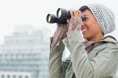 Pretty young model in winter clothes watching the city with binoculars Royalty Free Stock Image