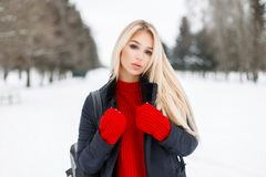 Pretty young model woman in an elegant winter coat. With a red fashion knitted sweater outdoors on a snowy winter day royalty free stock photo