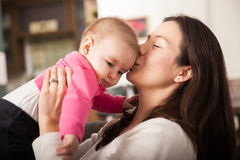 Pretty young mom kissing her baby girl Stock Photography