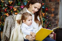 Pretty young mom reading a book to her cute daughter near Christmas tree indoors. Royalty Free Stock Photo