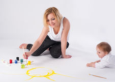 Pretty young mother and daughter draw picture Stock Images