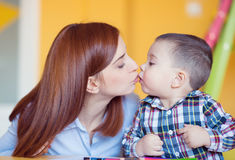 Pretty young mother kiss her baby son Stock Photos
