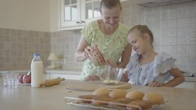 Pretty young mother and little cute daughter cook in the kitchen together. Happy family. Relationship mom and daughter. Beautiful young mother and little cute stock video footage