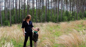 Pretty young mother looking down into smiling son's face while out in meadow Stock Photo