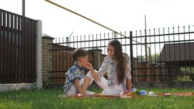 Pretty young mother with loose dark hair sits and feeds son. With raspberries on green grass close view slow motion stock footage