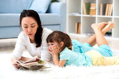 Pretty young mother reading book her little daughter, lying on the carpet on the floor in home stock photos