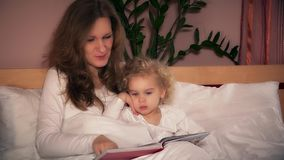 Pretty young mother reading book to her cute toddler daughter sitting in bed stock video