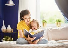 Mother reading a book. Pretty young mother reading a book to her daughter. Family holiday and togetherness royalty free stock photo