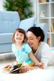 Pretty young mother reading a book to her daughter sitting on the carpet on the floor in the room. Reading with children royalty free stock photos