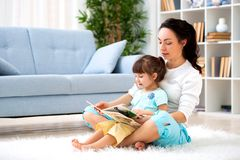Pretty young mother reading a book to her daughter sitting on the carpet on the floor in the room. Reading with children royalty free stock photo