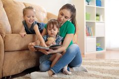 Pretty young mother reading a book to her daughters stock photography