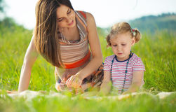 Pretty young mother reading book to her little daughter Stock Images