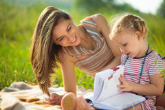 Pretty young mother reading book to her little daughter Royalty Free Stock Images