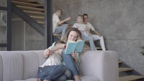 Pretty young mother reading book to her son while the rest of her teen kids playing with each other in the background stock footage