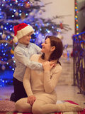 Pretty young mother sitting with her happy son in santa hat Royalty Free Stock Photography