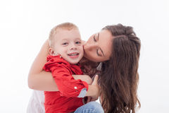 Pretty young mother is spending time with her. Cheerful women is embracing and kissing her son with love. The boy is smiling and looking forward with enjoyment Royalty Free Stock Photography