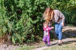 Pretty young mother walking with her daughter beautiful baby girl, and playing in the park among the trees and bushes Royalty Free Stock Photos