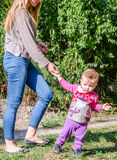 Pretty young mother walking with her daughter beautiful baby girl, and playing in the park among the trees and bushes Royalty Free Stock Image