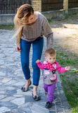 Pretty young mother walking with her daughter beautiful baby girl, and playing in the park among the trees and bushes Stock Photos