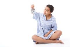 Pretty young mulatto girl holding alarm clock Royalty Free Stock Photos