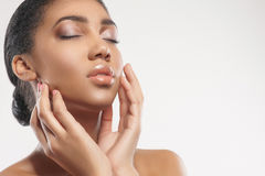Pretty young mulatto woman enjoying skincare treatment Stock Photos