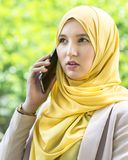 Pretty young muslim woman having a conversation on the phone. Stock Photo