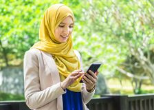 Pretty young muslim woman messaging using smartphone Stock Photo