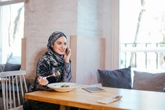 Young muslim woman talking on phone in cafe and looking on window. Pretty young muslim woman talking on phone in cafe and looking on window Royalty Free Stock Images