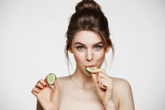 Pretty young natural girl with perfect clean skin looking at camera eating cucumber slice over white background. Facial Royalty Free Stock Images