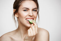 Pretty young natural girl with perfect clean skin looking at camera eating cucumber slice over white background. Facial Royalty Free Stock Photos